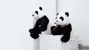 twee knuffels van panda's in een witte rieten mand foto