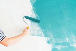 man kleurt muur blauw met een roller foto