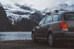 auto op de achtergrond van met sneeuw bedekte bergen en meren foto
