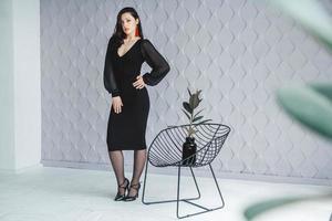 mode brunette vrouw draagt een zwarte jurk staande in de buurt van stoel foto