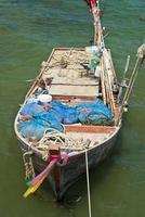 oude houten vissersboot in de zee foto