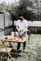 jonge man grillen kebab op spiesjes, man grillen vlees buitenshuis foto
