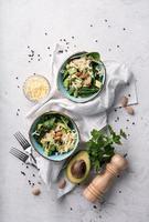 bovenaanzicht van frisse zomerse avocado- en spinaziesaladekommen foto