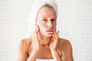gepreoccupeerde jonge vrouw die scrub op haar gezicht aanbrengt foto