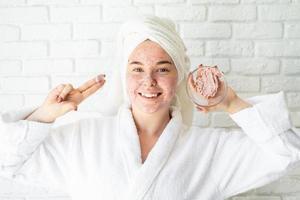 gelukkige jonge vrouw die gezichtsscrub op haar gezicht aanbrengt foto