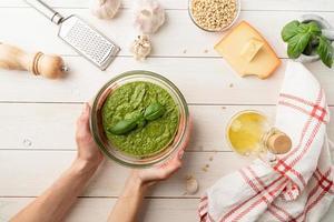 Italiaanse pestosaus bereiden. vrouw handen met zelfgemaakte pesto bowl foto