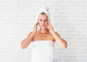 jonge vrouw in witte badhanddoeken die scrub op haar gezicht en nek aanbrengt foto