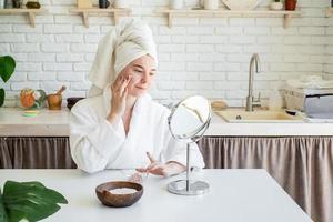 vrouw die gezichtsscrub op haar gezicht aanbrengt foto