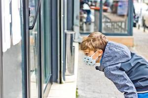 kleine jongen met gezichtsmasker kijken naar etalage in de stad. foto