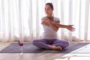 jonge vrouw die haar schouder uitrekt na yogabeoefening foto