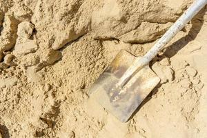 bovenaanzicht schop op zand in bouwplaats foto