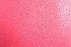 close-up waterdruppels op roze achtergrond foto