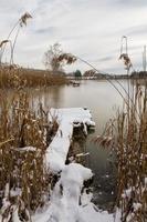 vissersbrug bedekt met sneeuw, uitzicht op een bevroren rivier foto