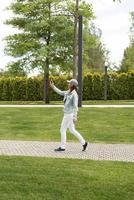 vrouw buitenshuis sms'en op haar mobiele telefoon, wandelen in het park foto