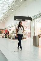 jonge vrouw die in het winkelcentrum loopt foto