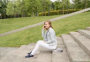 vrouw sms't op haar mobiele telefoon, zittend op de trap in het park foto