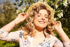 lachende zomervrouw met strohoed in park foto
