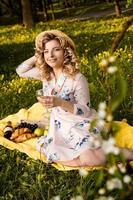 mooie jonge vrouw met blond haar in strohoed drinkt wijn foto
