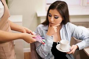 manicure demonstreert aan klantenpaletten met de kleur van de nagels foto