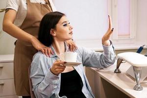 het meisje kijkt naar haar manicure tijdens de massage in de schoonheidssalon foto
