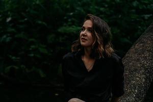 jonge vrouw - close portret in een donker bos. vrouw in zwart shirt foto