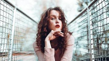 mode portret van trendy jonge vrouw zitten in de buurt van het gaas rabitz foto