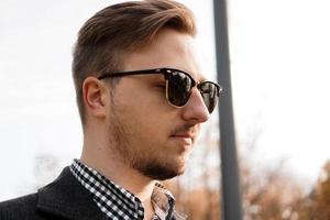 buitenshuis portret van jonge man met zonnebril foto
