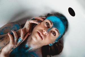 vrouw met glitters op haar gezicht. meisje in het bad foto