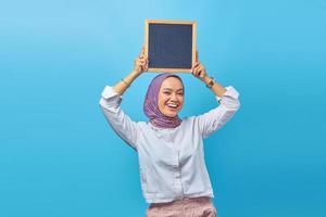portret van een aziatische vrouw die een bord vasthoudt met een lachende uitdrukking foto