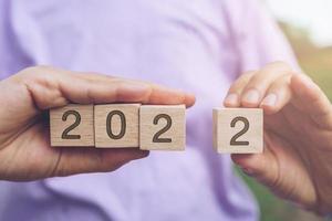 hand houden houten kubussen 2022 achtergrond, kopieer ruimte. doel begrip. foto