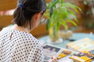 rijpe vrouw die fotoalbum bekijkt foto