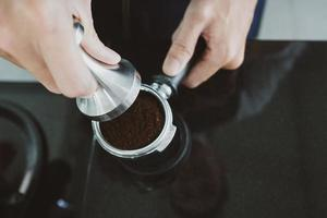 barista die espresso-gronden aanstampt foto