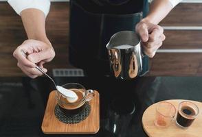 bariata die melkschuim in cappuccinokopje scheppen foto