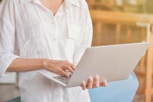 jonge vrouw die zilveren laptop gebruikt en vasthoudt foto