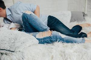 een stel in jeans en overhemden op een wit hangend bed foto