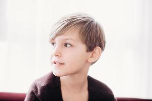 een close-up portret van een schattige jongen die op een bank tegen het lichte raam zit, soft focus foto