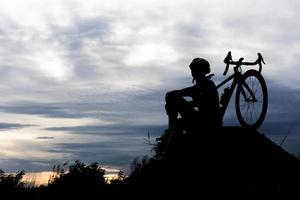 silhouet fiets fietsen man op de heuvel. ontspannen en sportconcept foto