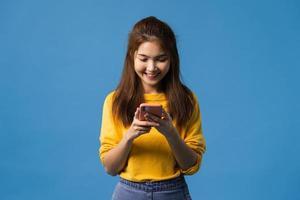 Aziatische dame met behulp van telefoon met positieve uitdrukking op blauwe achtergrond. foto