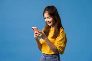 jonge dame met behulp van telefoon met positieve uitdrukking op blauwe achtergrond. foto