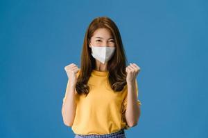 jong Aziatisch meisje dat gezichtsmasker draagt dat vredesteken blauwe achtergrond toont. foto