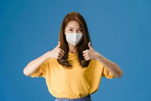jong Aziatisch meisje draagt een gezichtsmasker dat duim op een blauwe achtergrond laat zien. foto