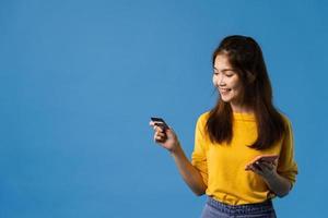 jonge aziatische dame die telefoon en creditcard op blauwe achtergrond gebruikt. foto