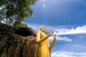 Boeddhabeeld op de berg en de boom en de prachtige blauwe lucht. foto