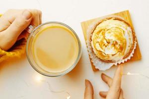 bovenaanzicht van taartje en koffie op witte tafel foto