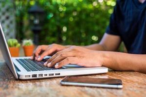 close-up mannelijke handen met behulp van laptop. foto
