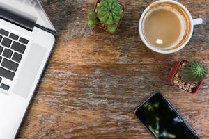 houten bureau tafel laptop, koffie, smartphone. foto