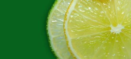 schijfje citroen en limoen en verse citrusvruchten op groene achtergrond. foto