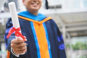 gelukkig afgestudeerd. gelukkig asain man in afstudeer toga's met diploma foto