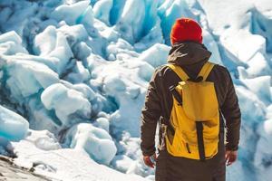 reiziger man staande op een rots op de achtergrond van een gletsjer foto