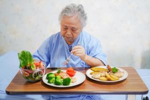 Aziatische senior vrouw patiënt eten ontbijt in het ziekenhuis. foto